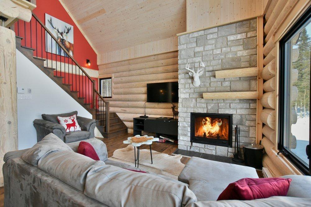 Chalet en bois rond Le Panache - Salon avec foyer