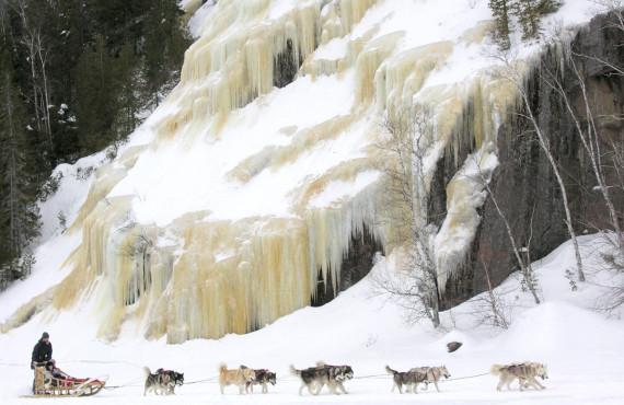 En traîneau à chiens longeant un mur de glace