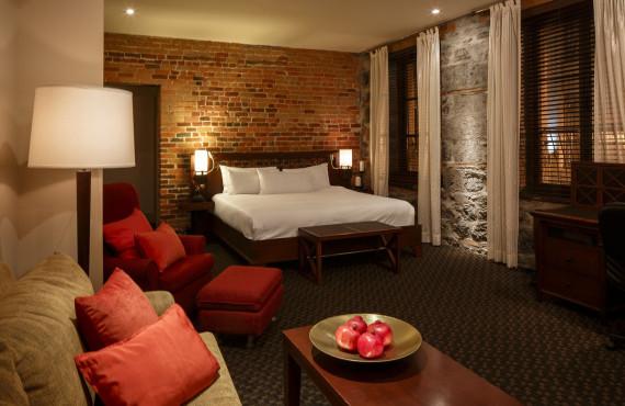 Chambre grand lit avec mur de brique