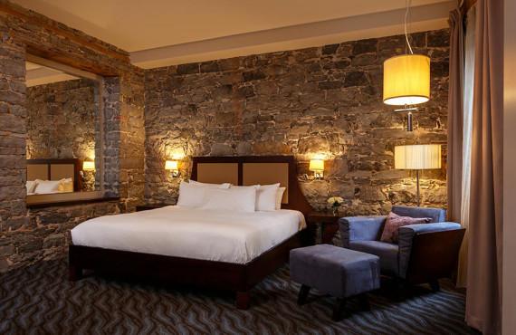 Chambre grand lit avec mur de pierre